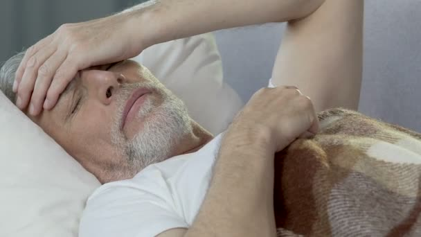 Old man lying in bed sleepless, holding hand against forehead, bad ...