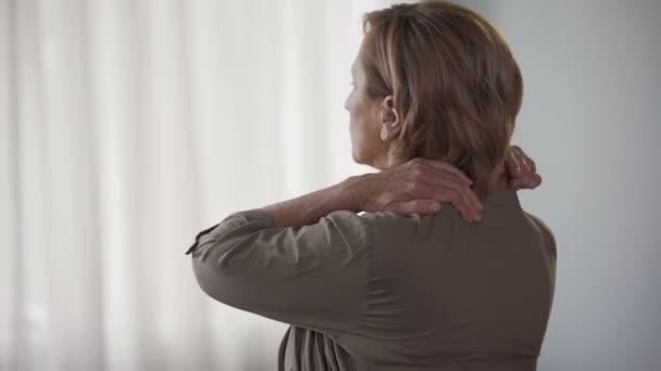 Ältere Frau steht nach hinten, reiben, Nacken und Schultern, steife ...