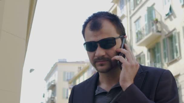 a3dae6f97b Empresario serio en gafas de sol hablando de smartphone en la calle de la  ciudad, lenta– metraje de stock