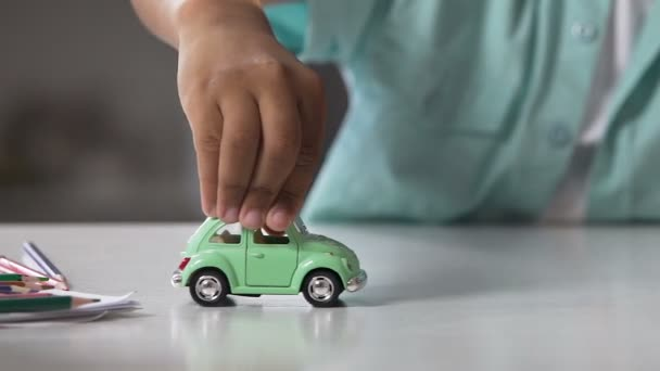 Mixed-race child rolling toy car over table surface, playtime, future dreams