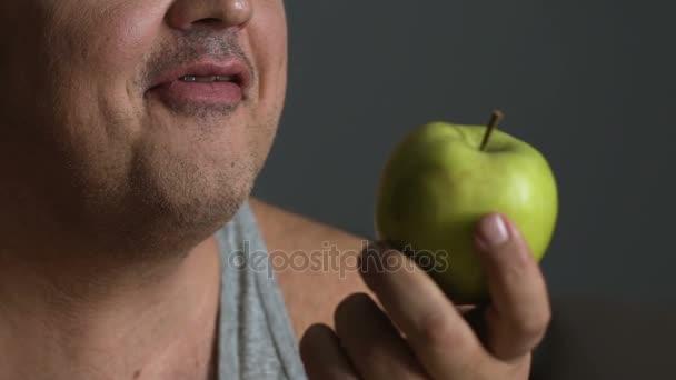 Diete Per Perdere Peso Uomo : Uomo che morde la mela fresca mantenendo una dieta sana per