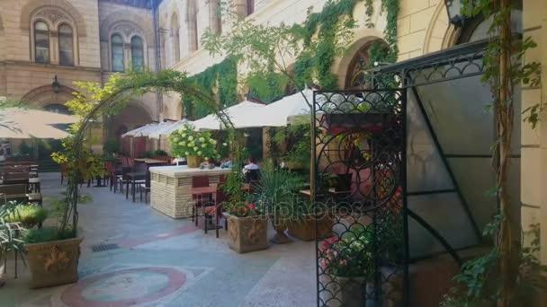 Accogliente caffetteria con terrazza con vasi di fiori e ombrelloni ...