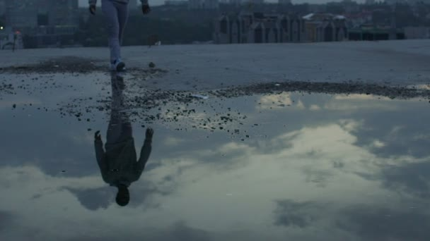 Sad man walking alone looking at reflections of gloomy sky ...