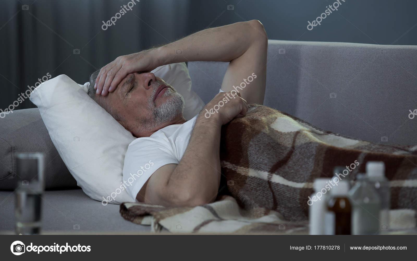Krank senior männlich im Bett liegend und schreckliche Kopfschmerzen ...