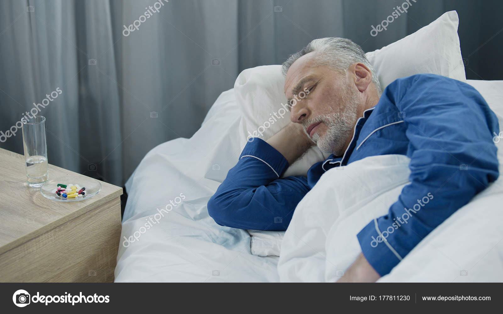 Grauen Haaren männlich schlafend im Bett nach Pillen nehmen, Rentner ...