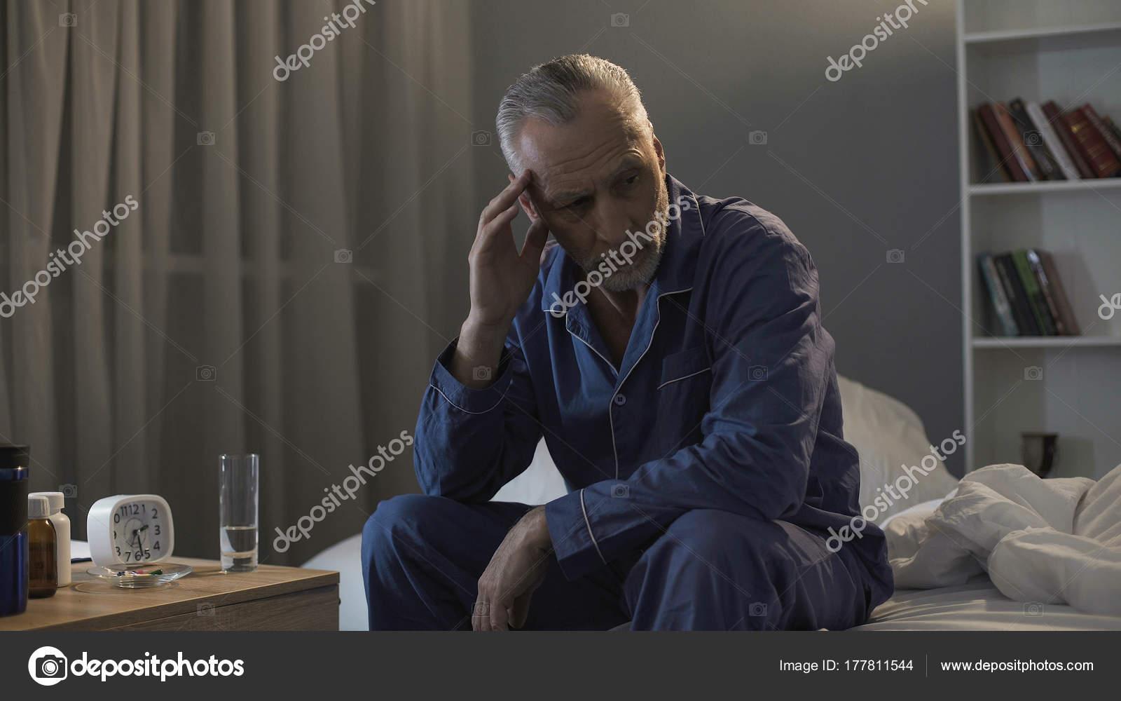 Senioren männlich im Bett sitzen und schreckliche Kopfschmerzen ...