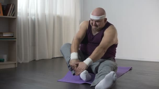 View Of Funny Overweight Man Doing Yoga At Home Trying To Sit In Lotus Pose