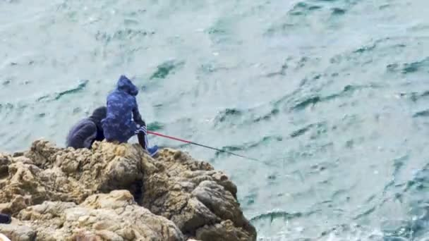 Two male teenagers fishing on the seaside cliff, hobby and relaxation,  nature