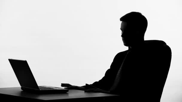 businessman silhouette sitting in front of laptop thinking on