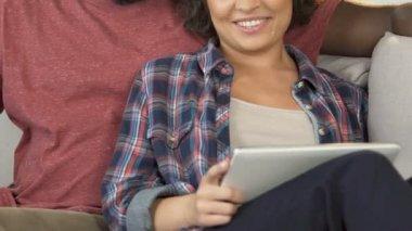 e8feaf1399 Namorado e namorada, sentado no sofá em casa e compras on-line sobre tablet