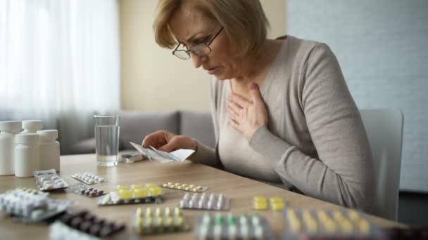 Femme triste en regardant tableau plein de pilules et soupirs, maladies de la vieillesse, la ...