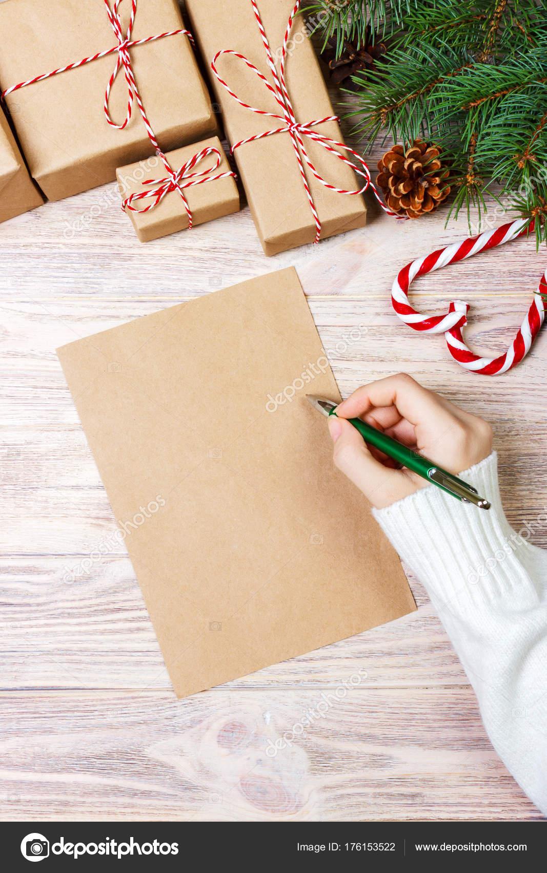 Weibliche Hände schreiben einen Brief an den Weihnachtsmann ...