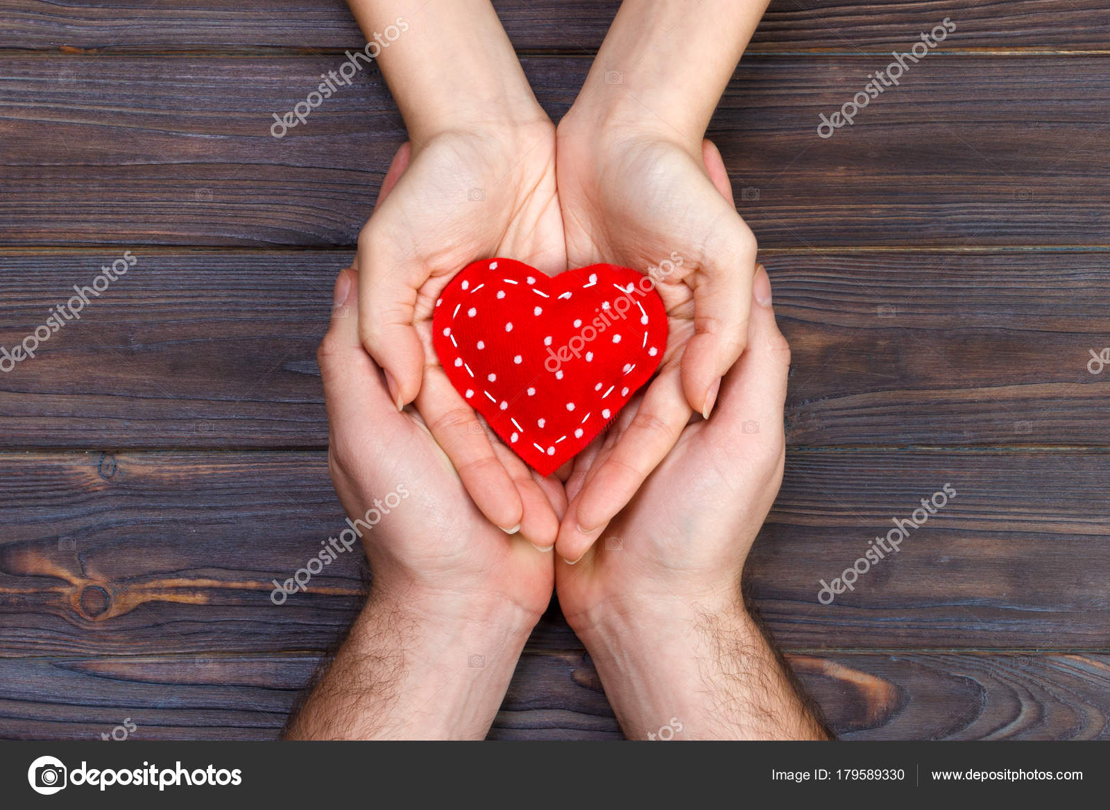 Red heart in woman and man hands,on wooden background — Stock ...