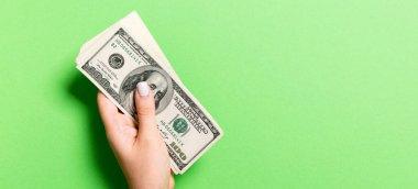 100 dolarlık banknotlar, fotokopi çekilen ellerde. Renkli arkaplanda para tasarrufu kavramının üst görünümü.