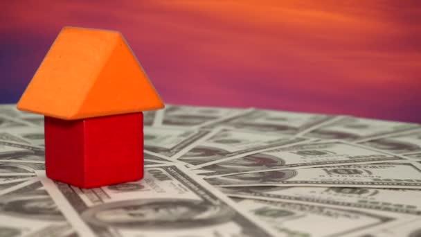 Nahaufnahme eines kleinen Hausmodells aus bunten Holzklötzen auf sich drehenden Dollarnoten