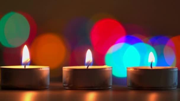 zblízka pohled na hořící svíčky a barevné pozadí bokeh