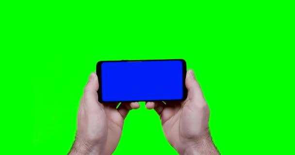 muž ruce drží smartphone s modrou chroma klávesou a zelené obrazovce na pozadí