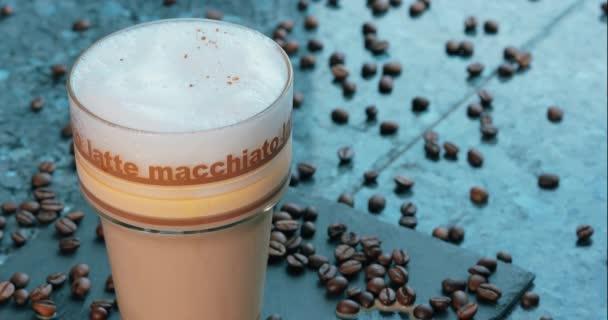 Nahaufnahme von Latte Macchiato, Kaffeehintergrund mit Bohnen, Kakaopulver in Glasschale