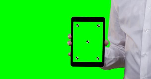 muž v bílé košili drží tablet do fotoaparátu se zelenou obrazovkou v popředí a na pozadí sledovacích bodů na tabletu
