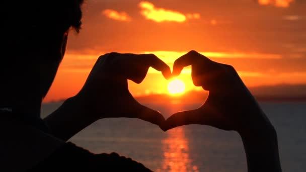 Fiatal nő, hogy kandalló szimbólum kezek naplementében