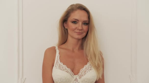 Szexi portré mosoly lány fehérnemű közelről. Dögös szőke melltartóban nézz a kamerába 4K.