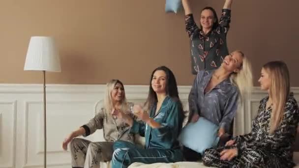 Many sexy women fighting pillow on bed in pajama closeup. Funny party friends 4K