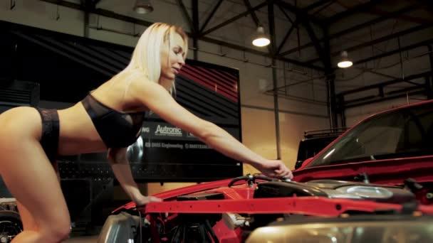 Sexy dívka dělat opravy auto v garáži zblízka. Horké blondýny mechanik v podprsenka 4K.