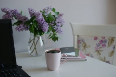 cup of tea with glass vase with purple lilac and laptop with books on table background