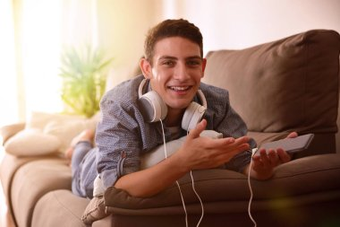 Teen with headphones on couch face surprised and laughing