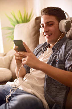 Teenager watching multimedia content with headphones on couch cl