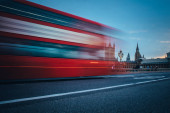 Fotografie Scene of Westminster Bridge seen from South Bank, quiet morning double decker bus and fast moving routemaster bus present.