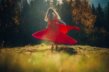 Mysterious sorceress in a beautiful red dress. Her hair and dress are fluttering in the wind. Background bright, autumn, fiery forest trees with warm tones.
