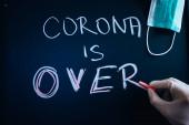 CORONA OVER, szöveg krétával írva a fekete iskolai fórumon