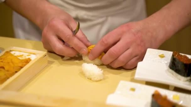 Großaufnahme der Hände eines Küchenchefs in einem schicken Restaurant bei der Zubereitung eines Brettes traditioneller japanischer Küche - Nigiri-Sushi mit Seeigel