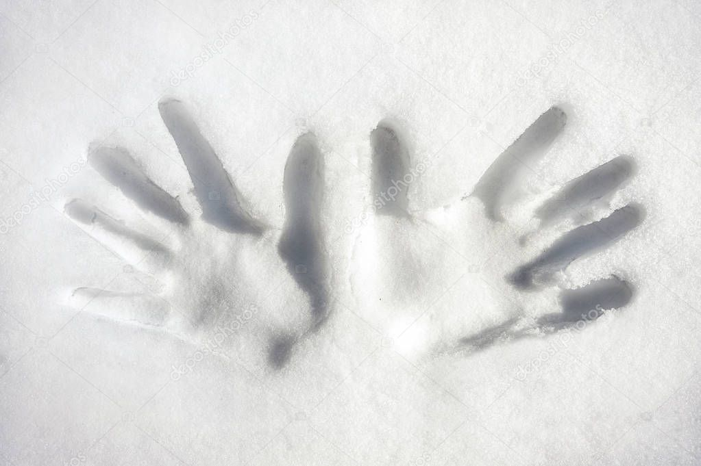 Two hands/palms print on white snow surface. Outdoors image