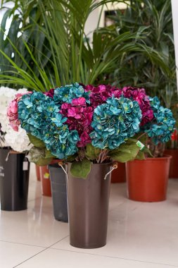 Artificial flowers are hydrangea turquoise and crimson. Artificial flowers stand on a floor in a vase.