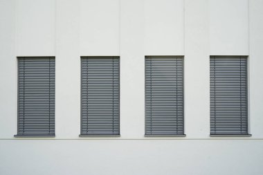 Four narrow windows with closed gray role shutters on the light wall.