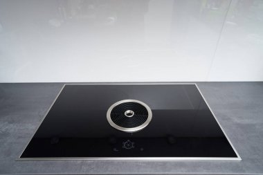 Induction cooker with black glass surface and integrated cooker hood