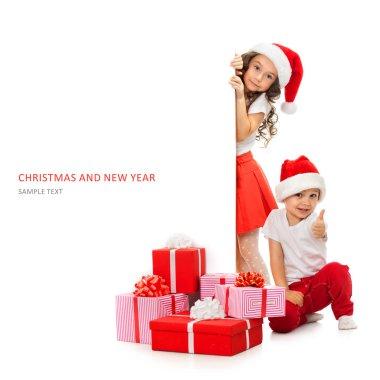 Kids in Santa hat peeking from behind blank sign billboard