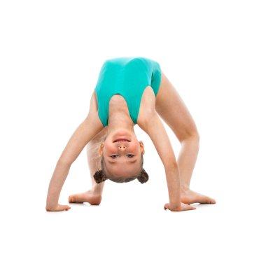 Flexible little girl gymnast doing a bridge on white background