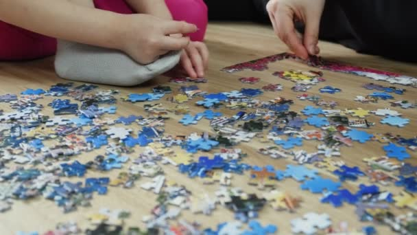 Family makes a puzzle at home on the floor. Top view, slow motion