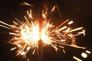 Close-up of a burning sparkler on a black background.