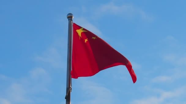 The Chinese flag on a metal flagpole is developing in the wind against a blue sky.