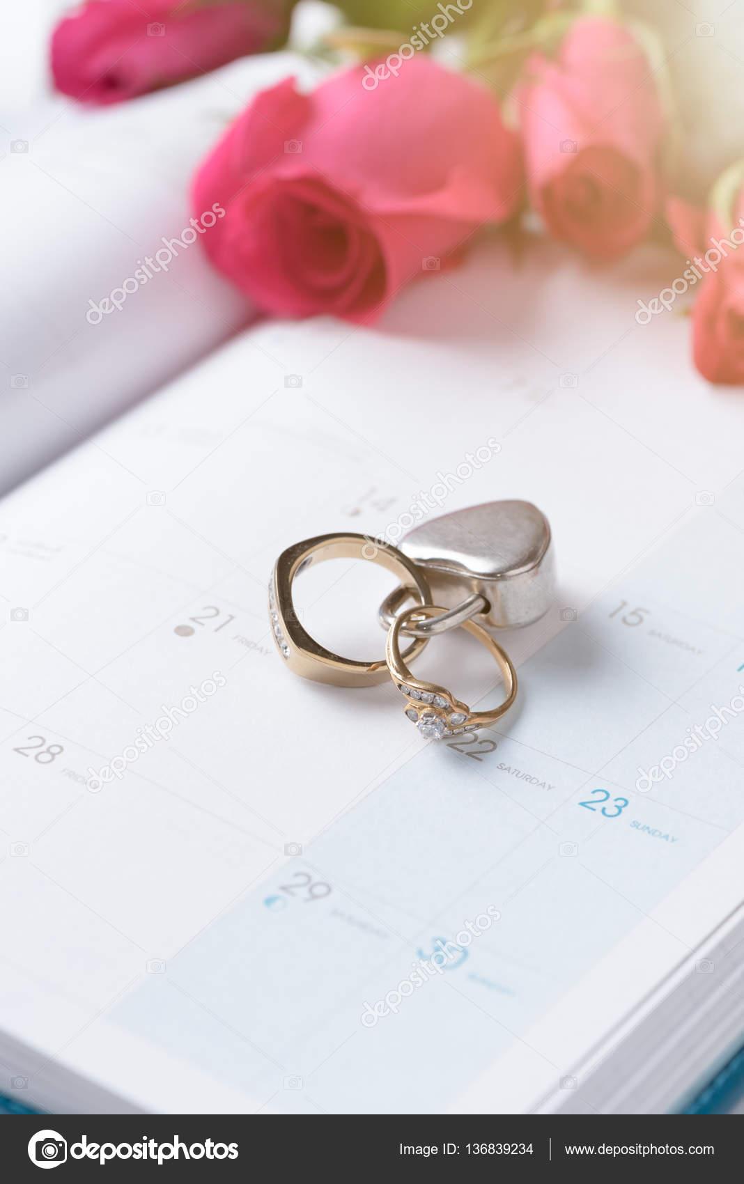 0afd50260cbd Boda anillos de oro trabado con bloqueo en el calendario y fondo de color  de rosa rojo — Foto de kwanchaichaiudom