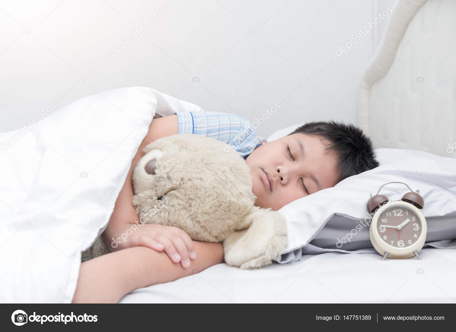 Obese fat boy sleep and hug teddy bear on bed stock photo