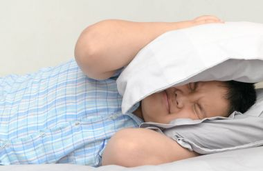 Obese fat boy lying in bed covering head with pillow