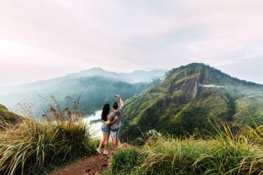 A couple in love is photographed on the phone. Boy and girl in the mountains. Man and woman holding hands. The couple travels around Asia. Travel to Sri Lanka. Serpentine in the mountains. Lover