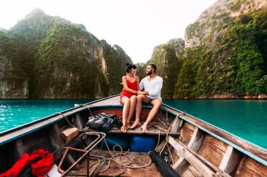 A couple in love travels by boat to the Islands. Honeymoon trip. Honeymoon on the Islands. Guy and girl swim in the lagoon. Man and woman floating on the Bay. Couple travels in Asia. Wedding travel