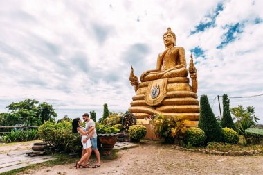 A couple in love travels around Asia. Guy and girl in Thailand. Travelers near the Buddha statue. Big Buddha. Golden Buddha. Man and woman traveling. Couple on a tour. Wedding travel