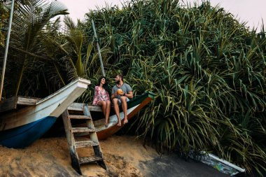 Honeymoon trip. Couple in love on the seaside drinking coconut. Couple on the shore of Paradise island. Man and woman in the Bali. Relax on the island. Holiday romance. Travel to Asia. Happy couple